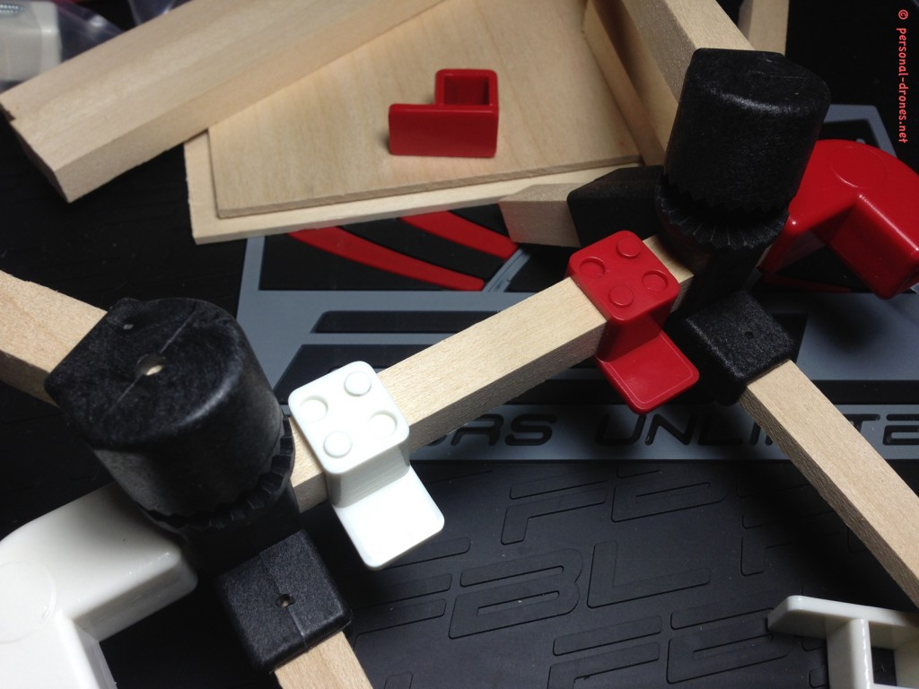 "A fist test of Quadlugs components assembly. From left to right, assembled on a frame ""side bar"", angle lug, arm lug, plate lug white, plate lug red, arm lug, angle lug red. See how the colors will beautifull help in assessing the quad orientation durintg flight. At this time the plate lugs were still not glued in pairs"